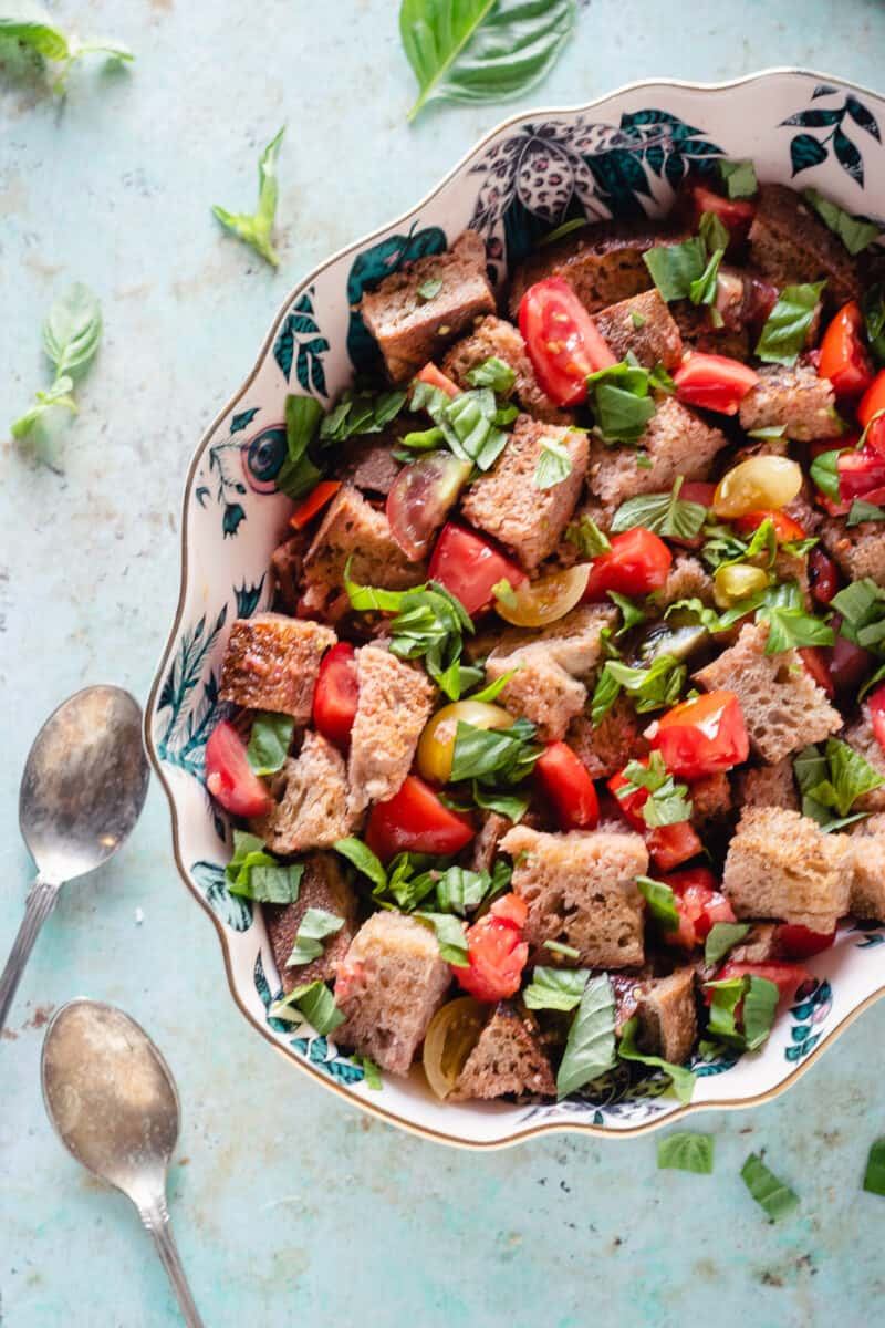 Panzanella in a patterned oval bowl with a pair of serving spoons on the counter beside it