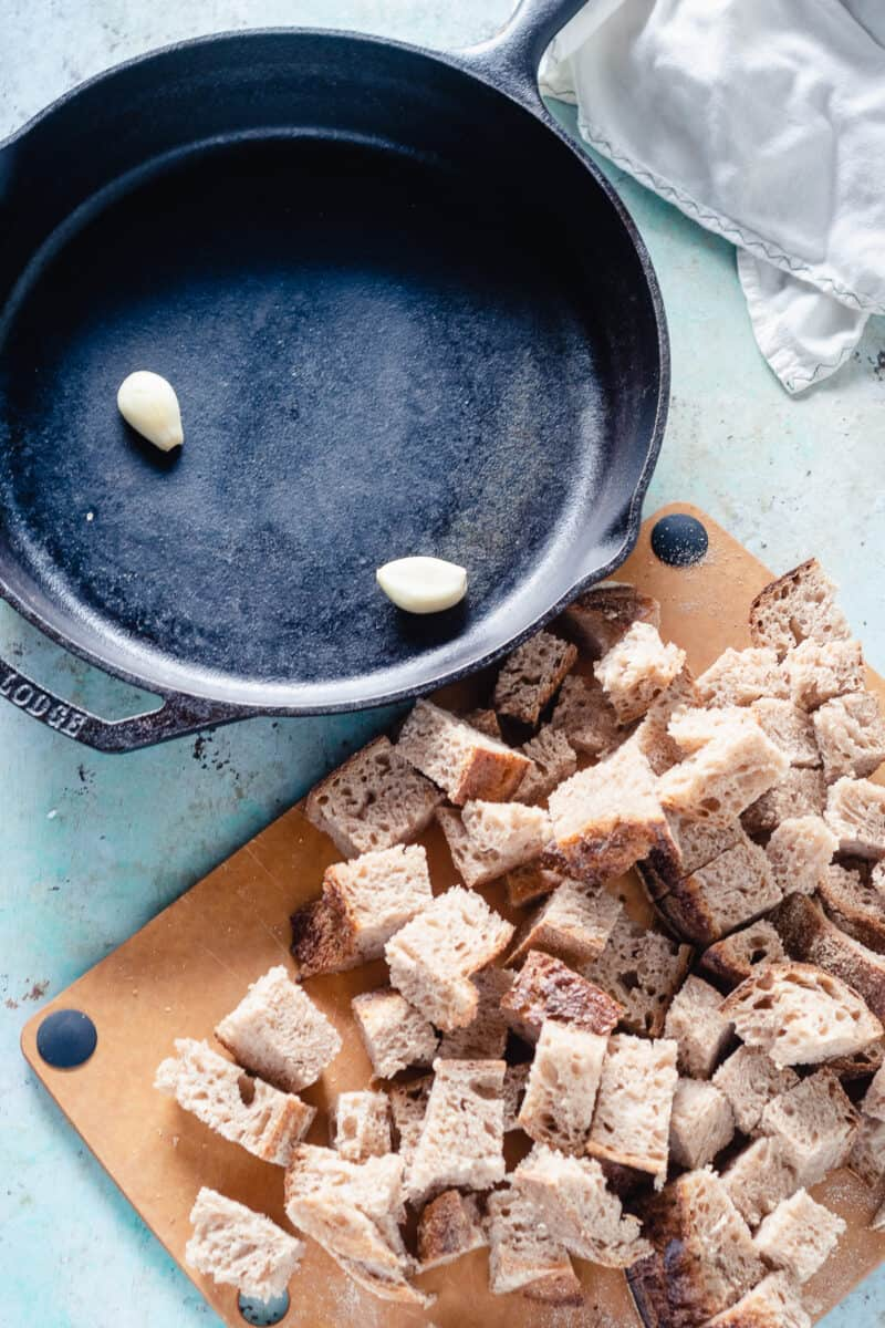 Garlic cloves in a cast iron skillet and cubes of bread on a cutting board next to it
