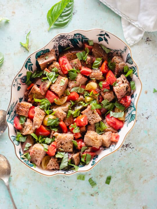 Panzanella in an oval bowl with basil scattered around