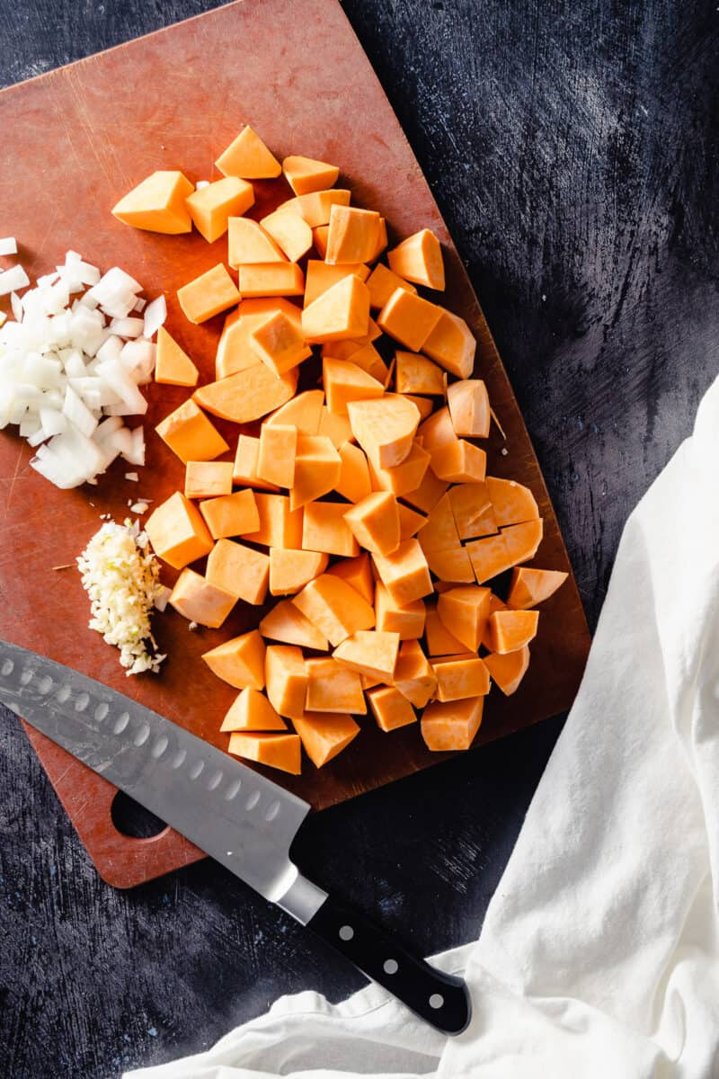 Diced sweet potatoes, onions, and garlic on a cutting board