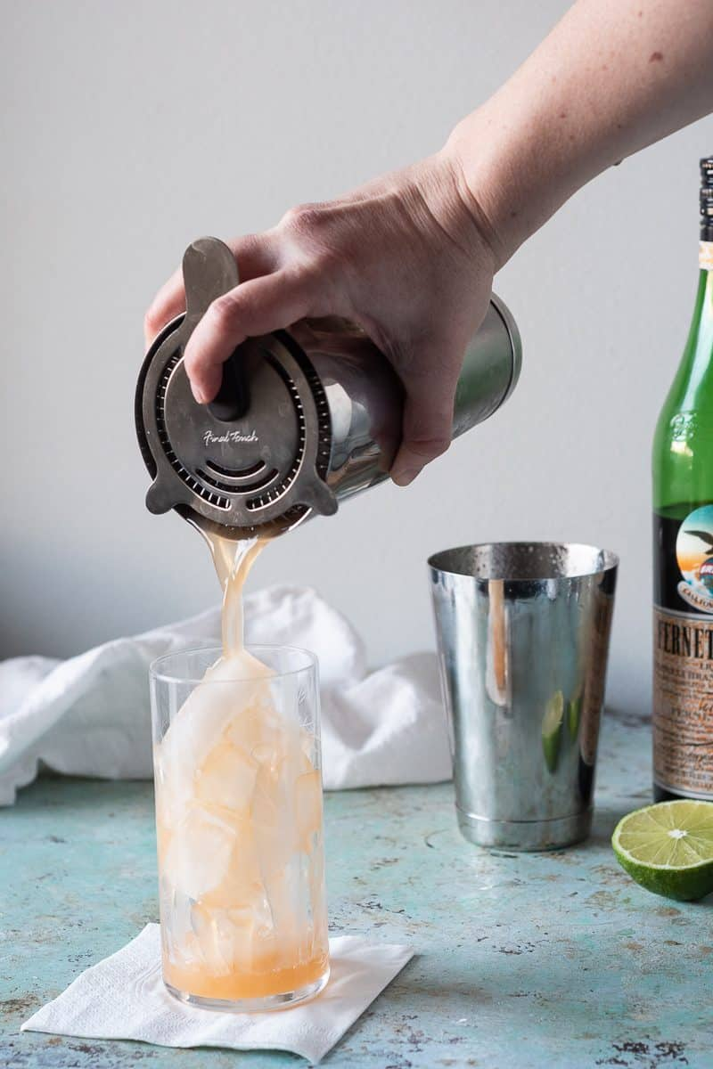 Straining a Kingston Club cocktail