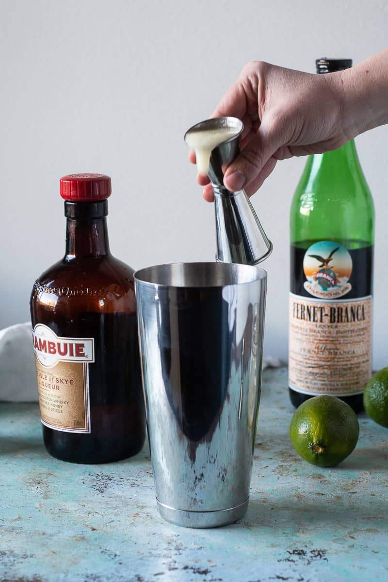 Pouring lime juice from a jigger into a cocktail shaker