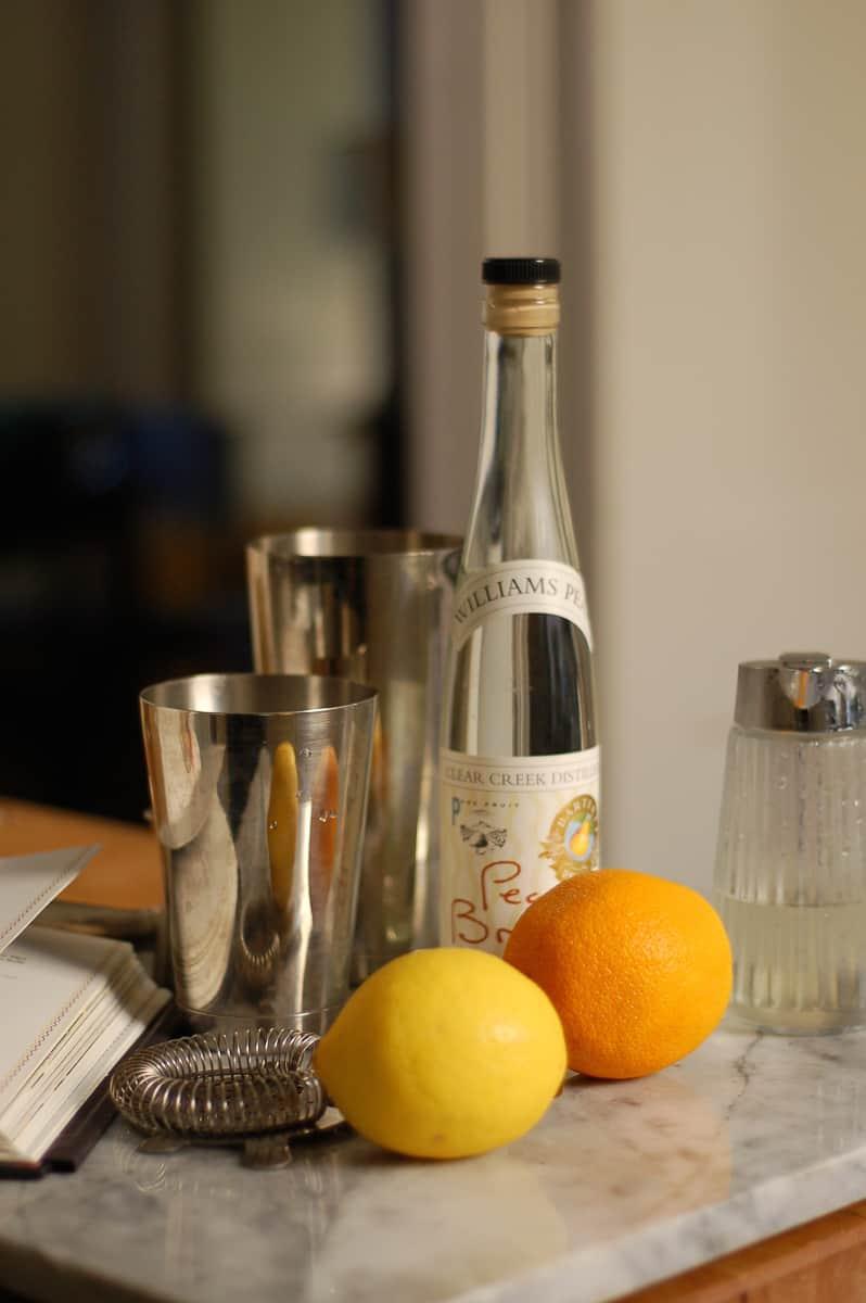 Cocktail shaker, orange, lemon, and pear brandy