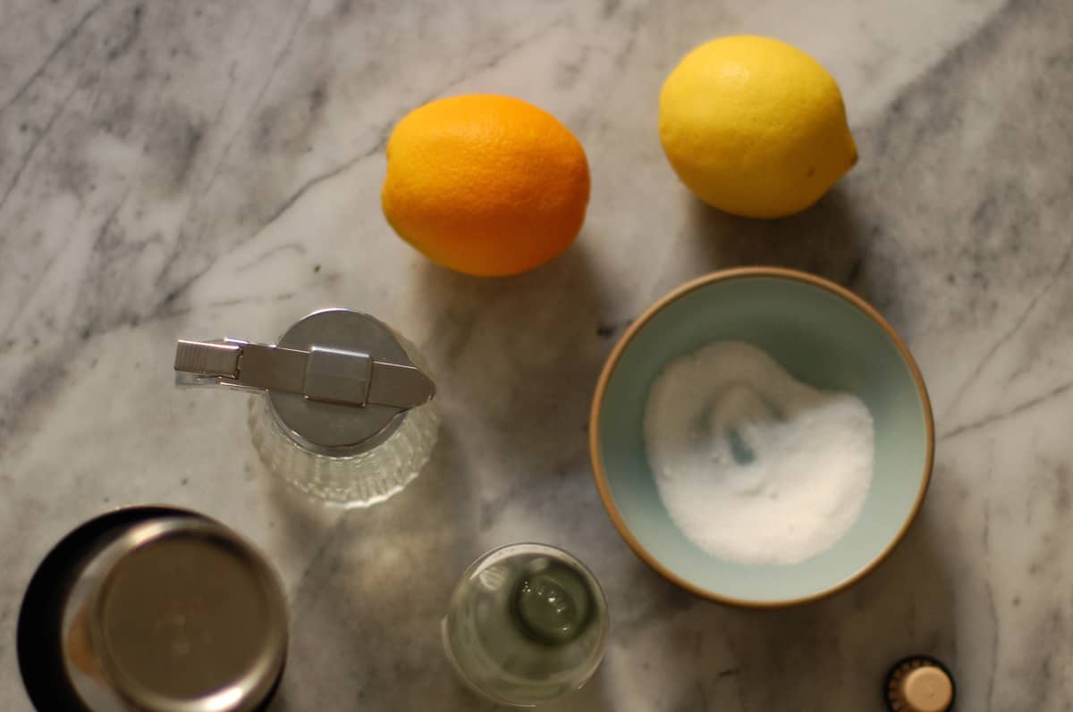 Simple syrup, orange, lemon, and bowl with sugar
