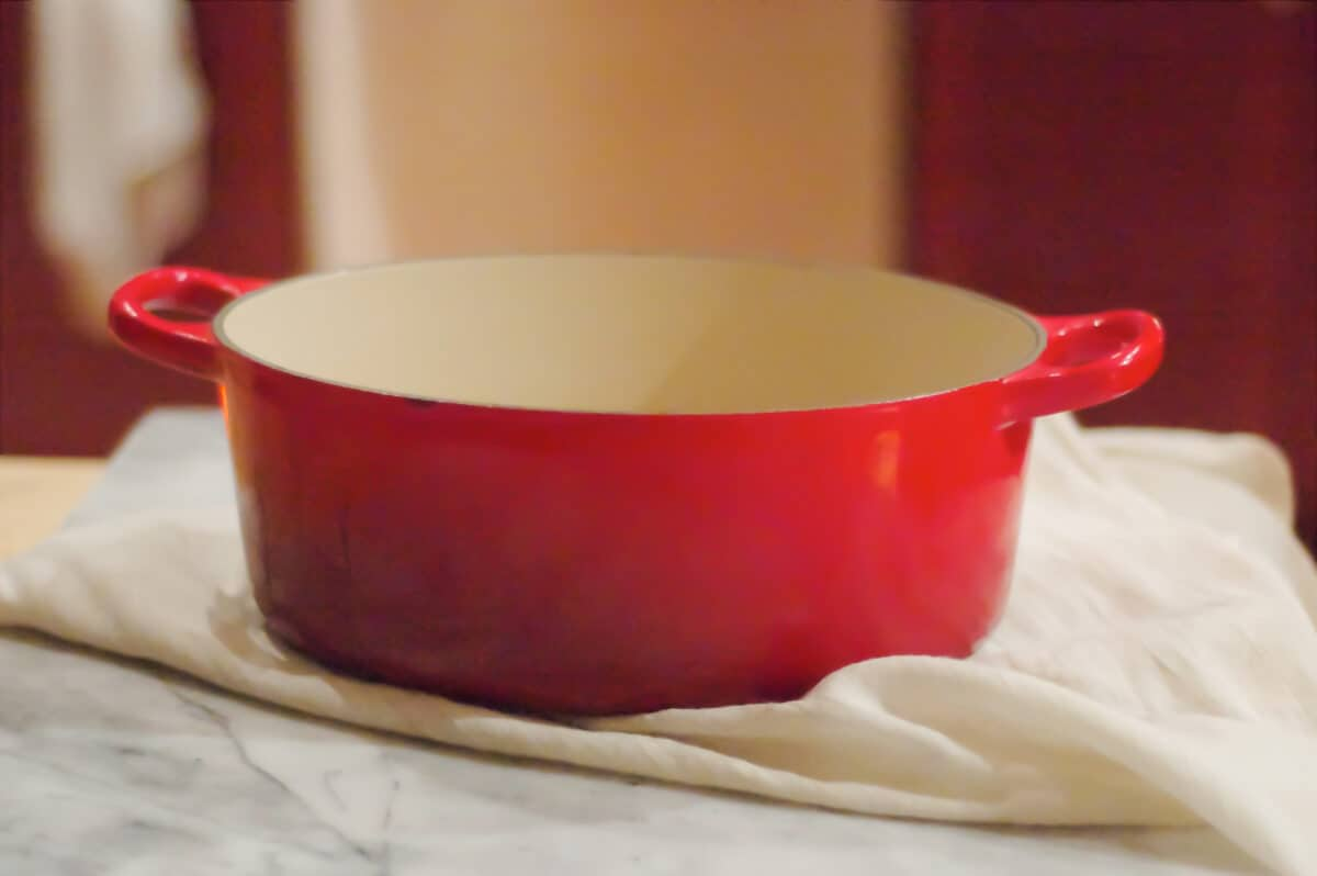 A red Dutch oven on a kitchen towel