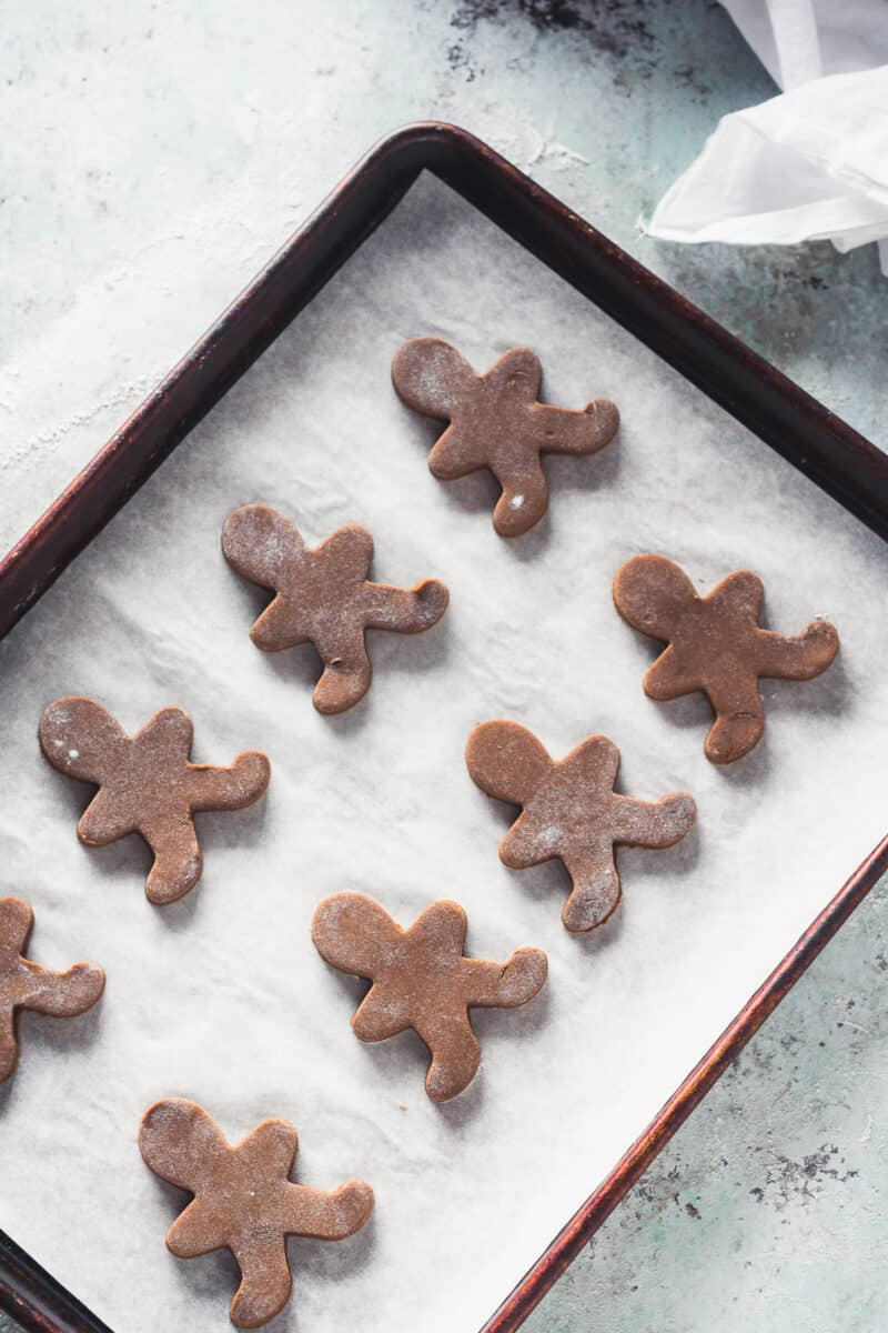 Gingerbread men on a baking sheet waiting for decoration