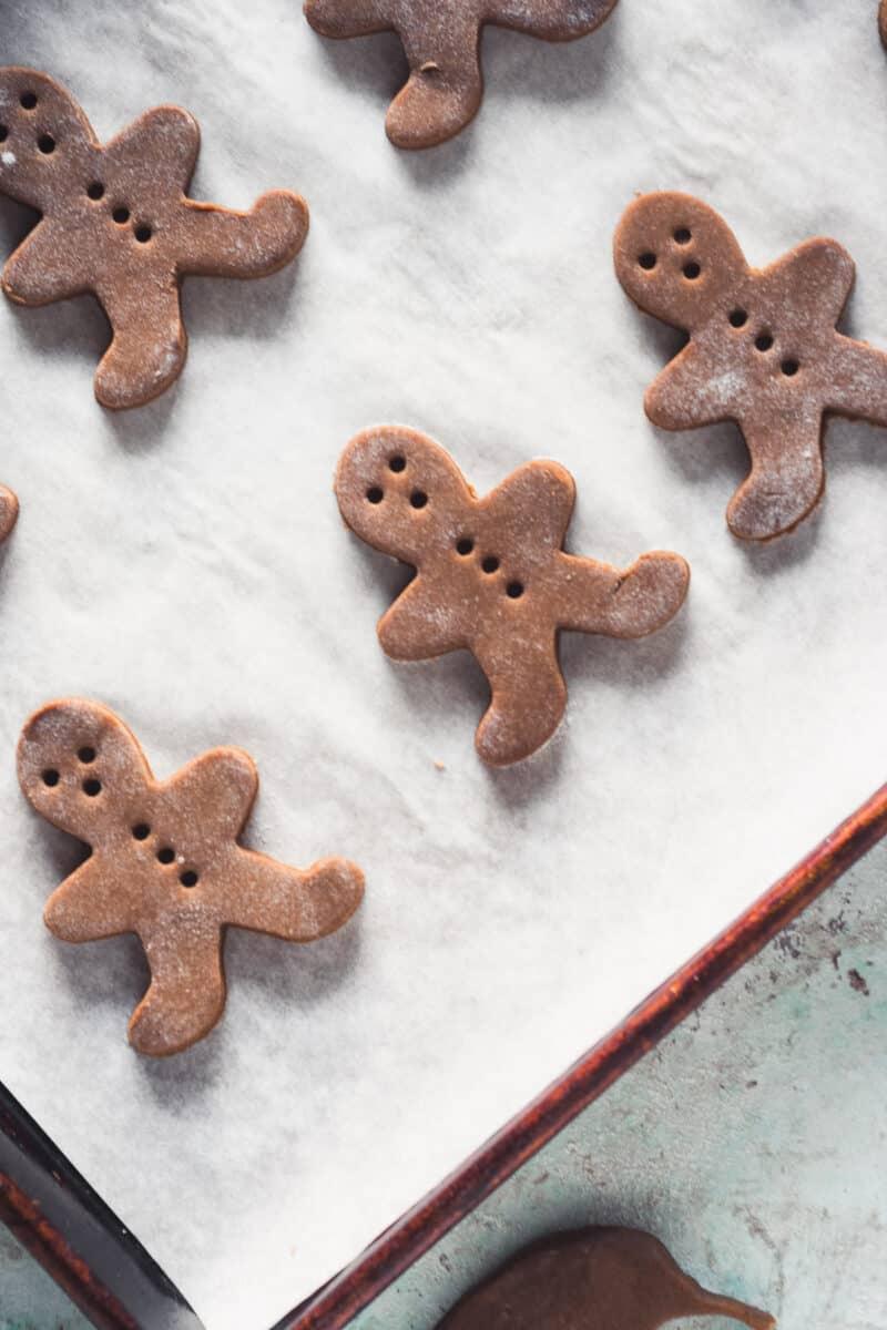 Cut-out gingerbread men dough on a baking sheet