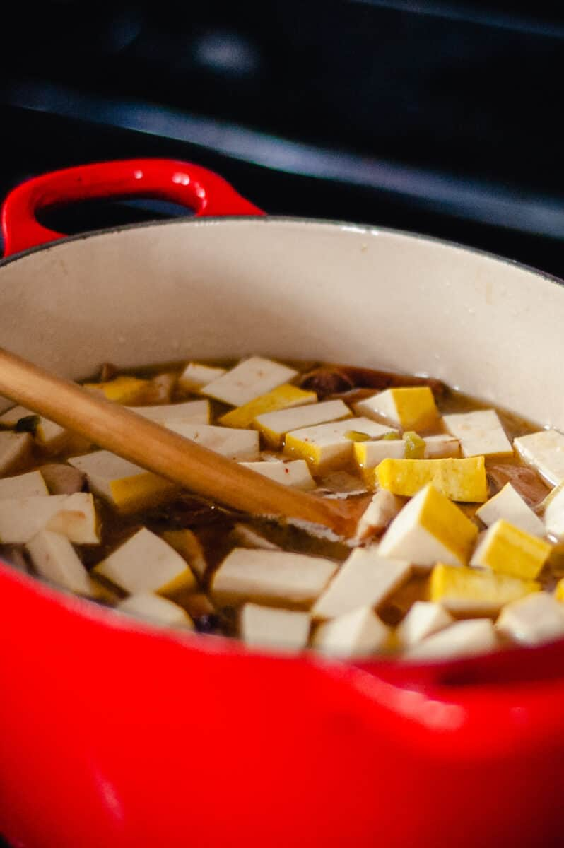 Tofu in hot and sour soup in a red Dutch oven