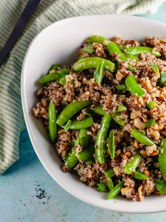 Sugar Snap Pea and Cashew Quinoa in a n oval serving bowl with a serving spoon next to it