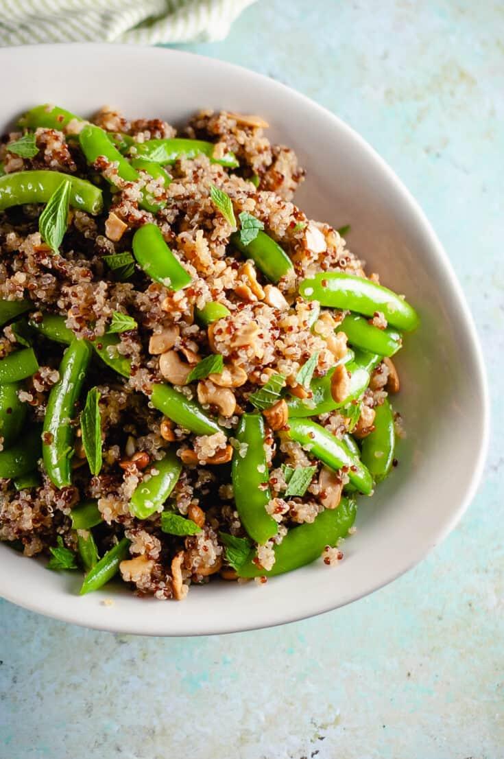 Sugar snap pea and cashew quinoa salad in a serving bowl, closeup