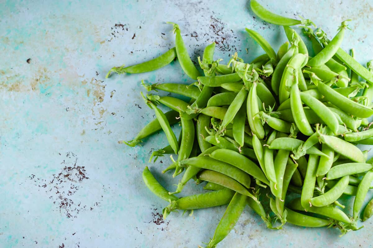 Sugar snap peas piled on a counter