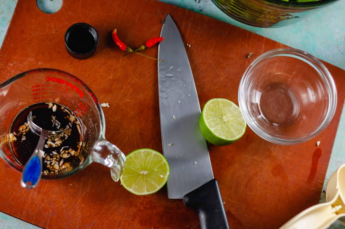 Soy sauce and minced garlic in a glass measuring cup, a lime sliced in half on a cutting board with a chef's knife