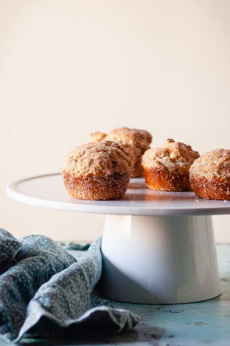 Cinnamon Sugar Oat Muffins on a white cake stand