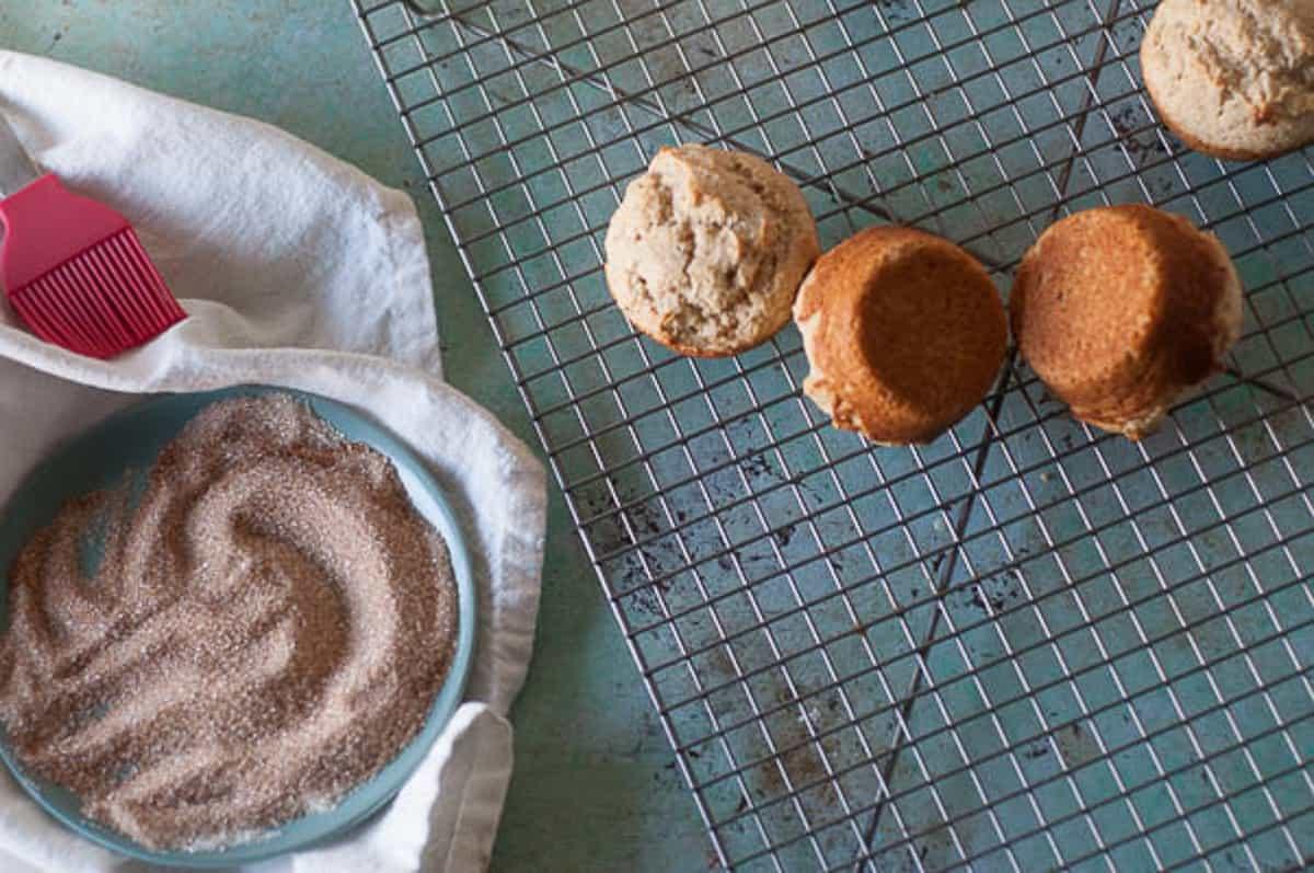 Cinnamon sugar next to warm muffins