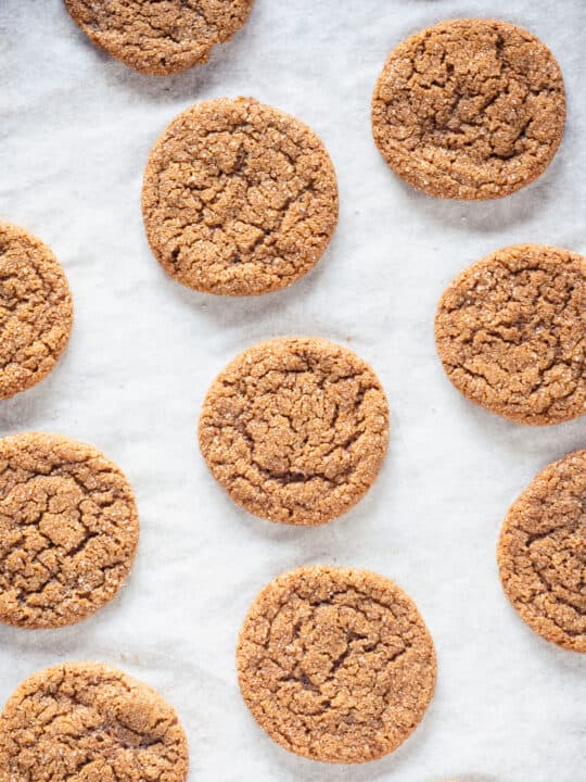 Chewy Citrus Molasses Spice Cookies on parchment paper
