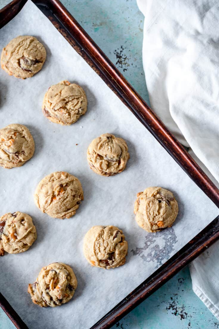 Chocolate butterscotch chip cookies on a parchment lined sheet pan