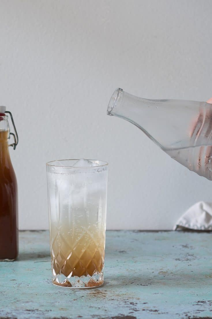 Adding soda water to ginger syrup to make ginger ale