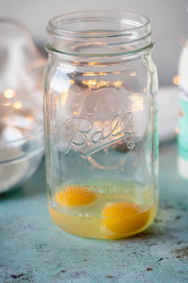Two eggs cracked in a mason jar