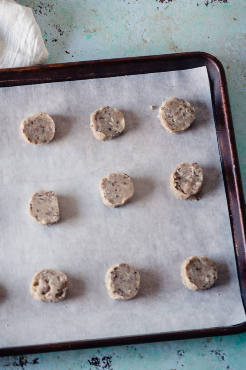 Unbaked nibby buckwheat cookies on a sheet pan