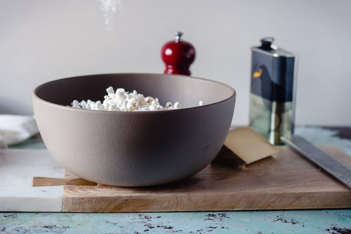 Shredded pecorino cheese being sprinkled over popcorn