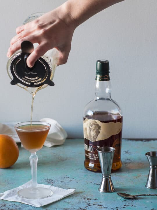 Revolver Cocktail being strained into a glass with jiggers, an orange, and whiskey and coffee liqueur in the background