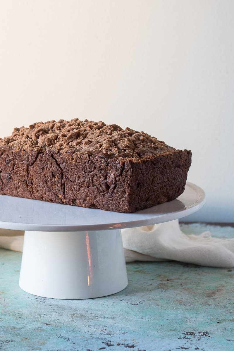 Streusel-topped Banana Bread with Chocolate and Pecans on a cake stand, side view