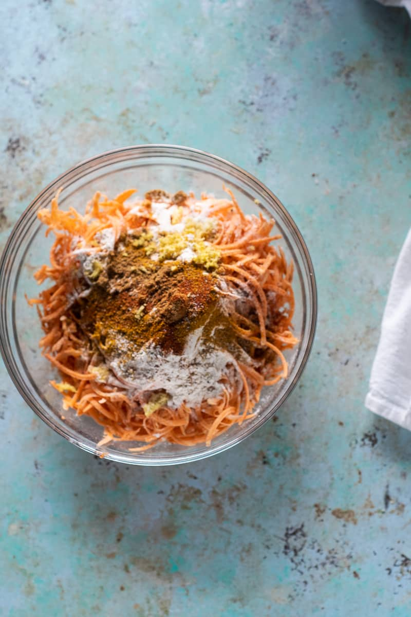 Shredded sweet potatoes, flour, and spices in a bowl