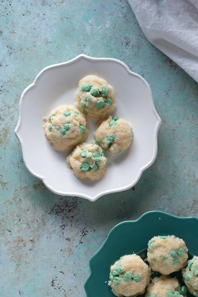 Mint chip cookies on a white plate with some more cookies on a green plate nearby