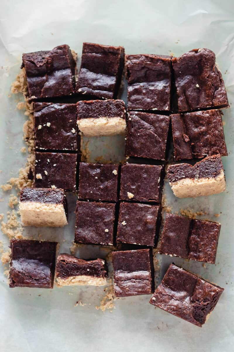 Sliced almond shortbread brownies with a few turned sideways to show the layers of shortbread crust and brownie topping