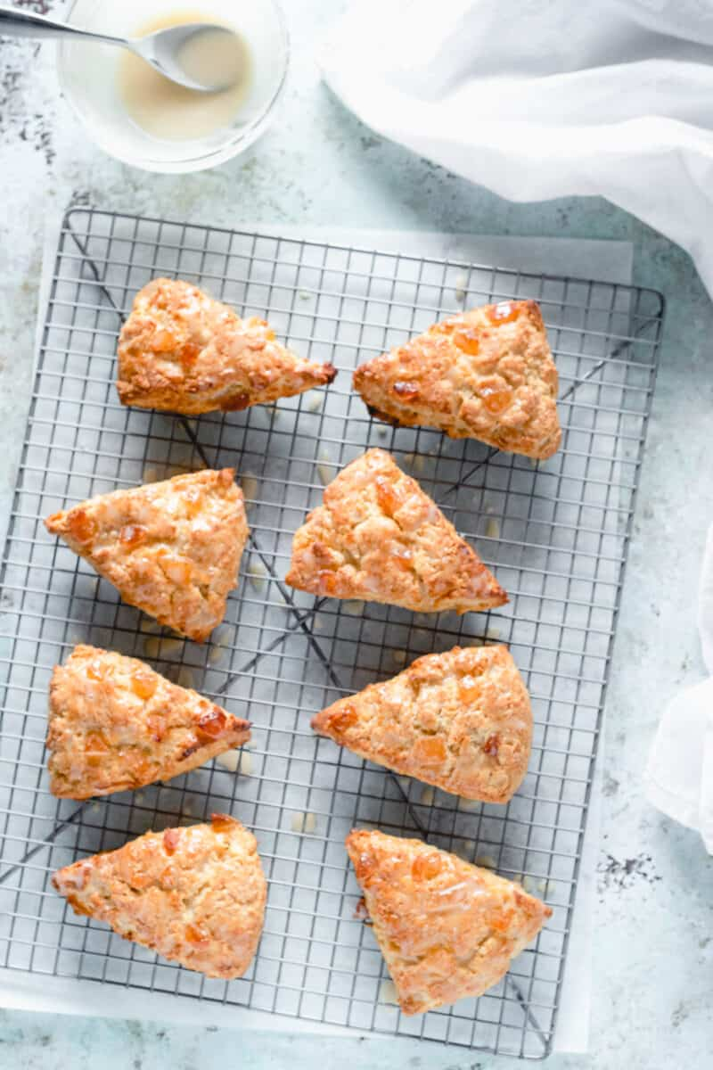Orange ginger scones on a cooling rack with a bowl of creme fraiche icing alongside