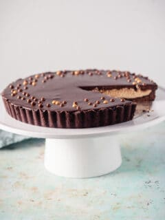 Chocolate Peanut Butter Tart on a white cake stand