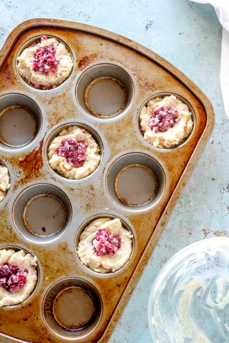 Raspberry lemon muffins in a muffin tin before baking