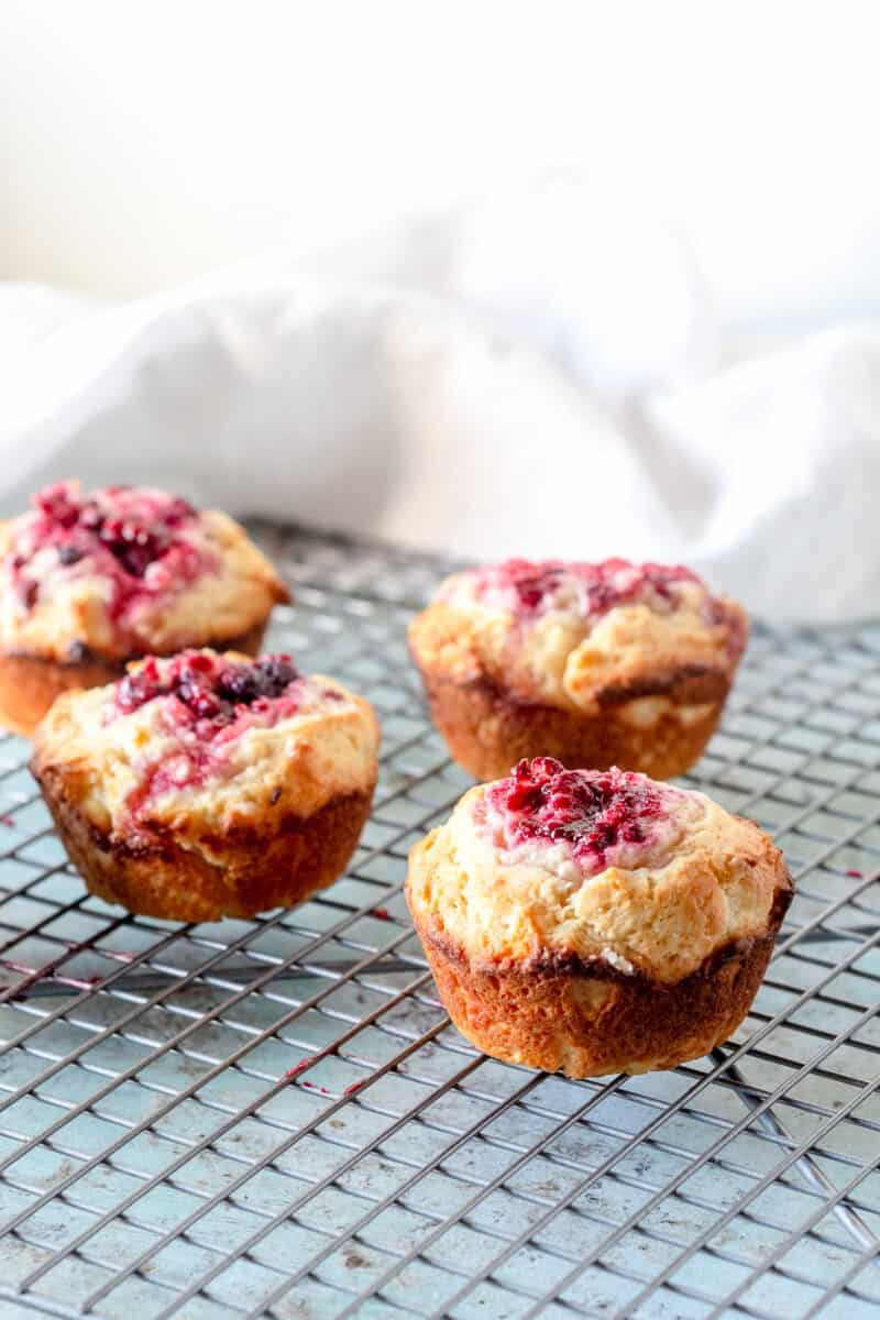 Raspberry lemon muffins on a cooling rack, side view