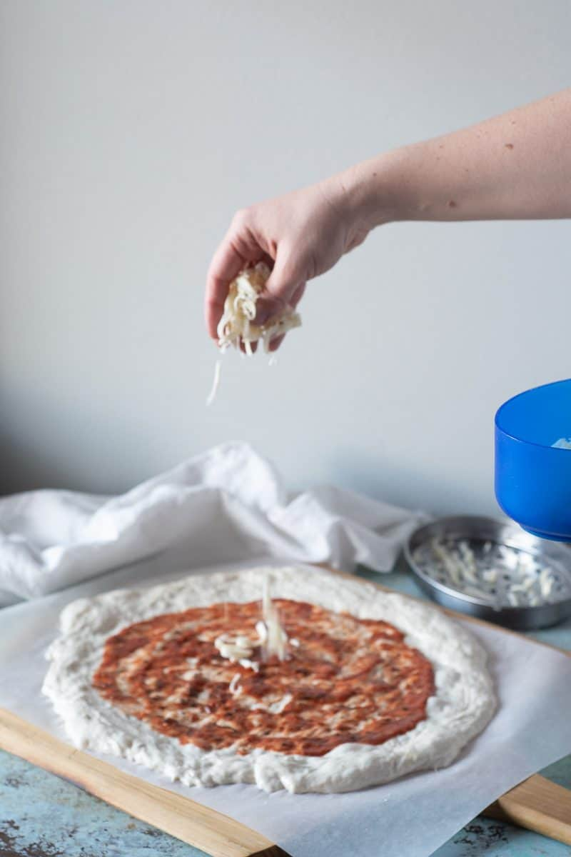 Adding cheese to a sauced round of pizza dough