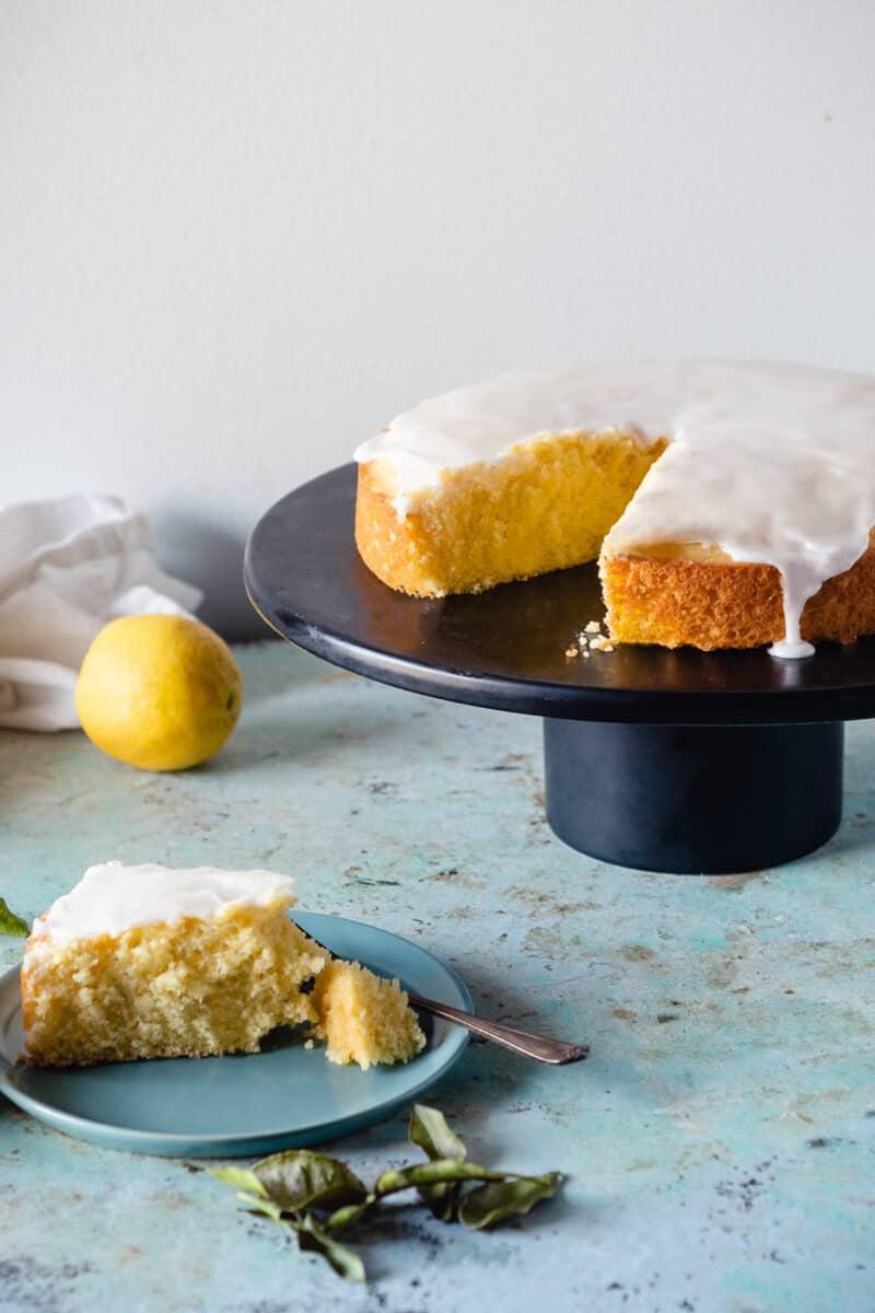 Makrut Lime Leaf Cake on a black cake stand with a slice of cake on a plate alongside it