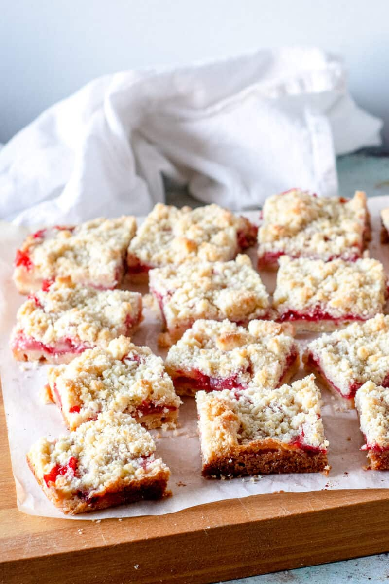 Sliced strawberry crumb bars, side view, on a cutting board