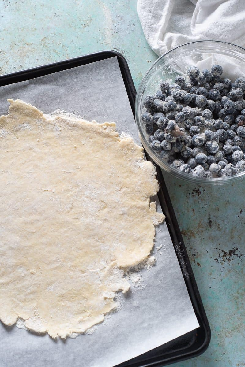 Rolled out galette dough and blueberry filling in a bowl
