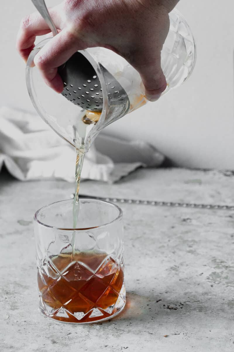 Straining a Manhattan cocktail into a glass