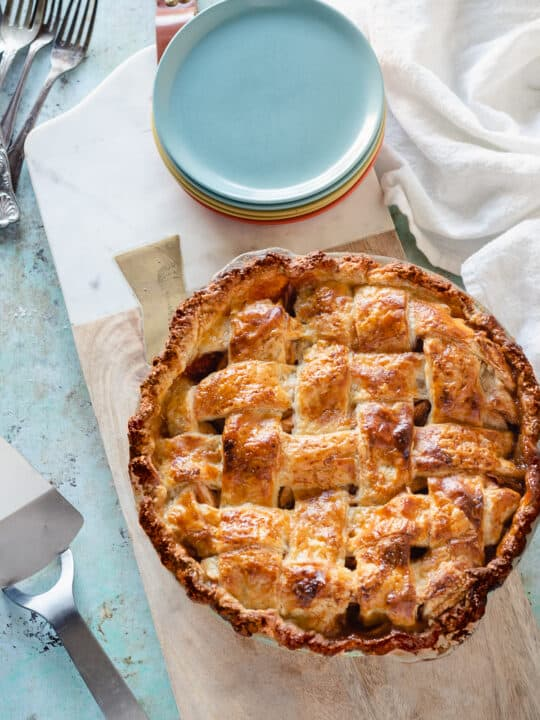 Apple Pie with a lattice top crust on a serving board with a stack of dessert plates next to it
