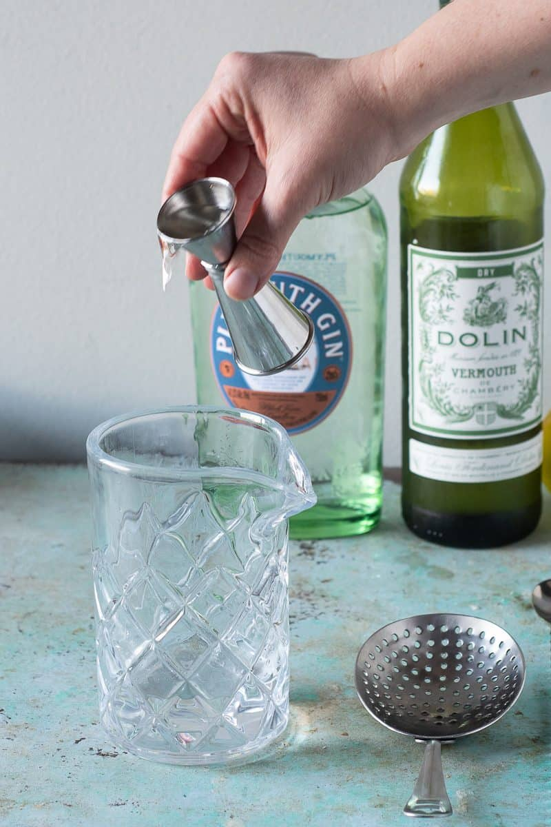 Gin being added to a mixing glass