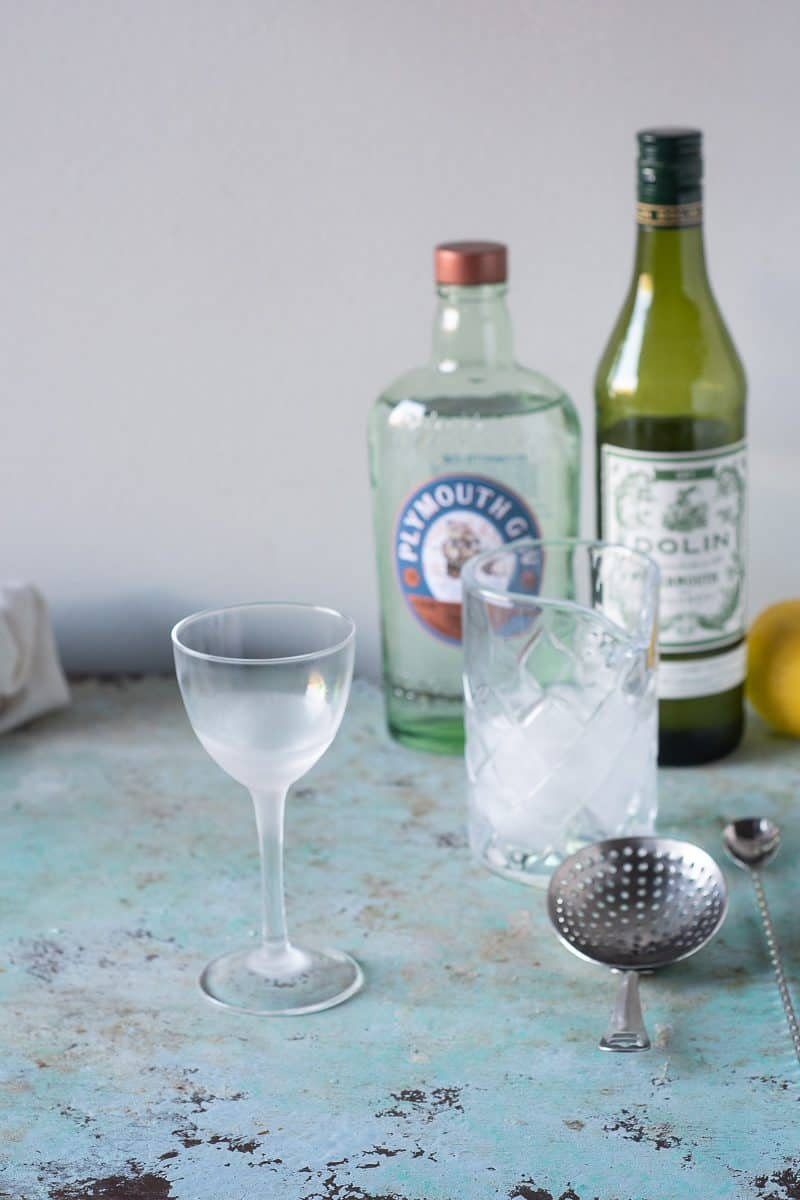 Chilled Nick and Nora glass next to a mixing glass with ice
