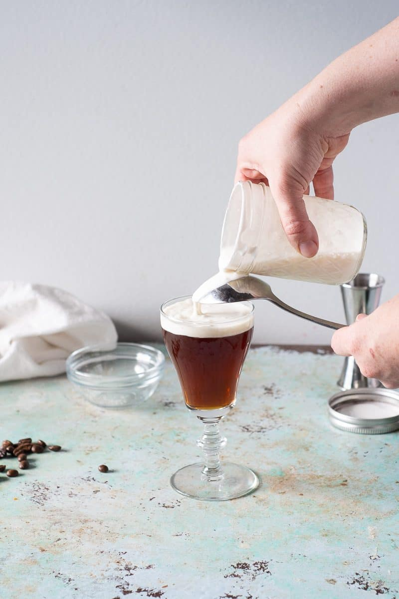 Pouring gently whipped cream over the back of a spoon to top an Irish coffee