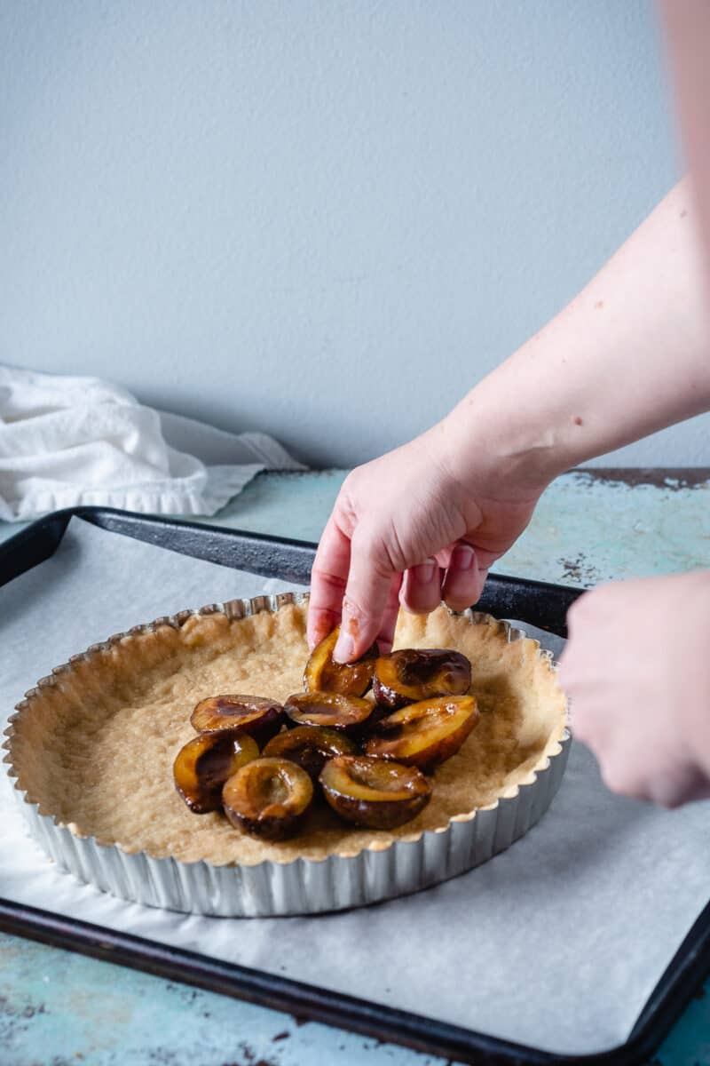 Hand putting plums on a tart crust