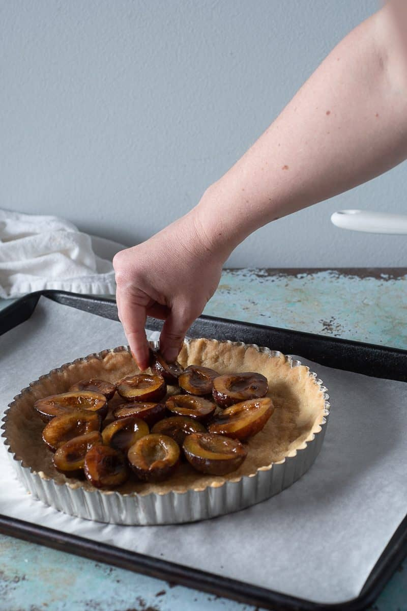 Plums being arranged on a tart crust