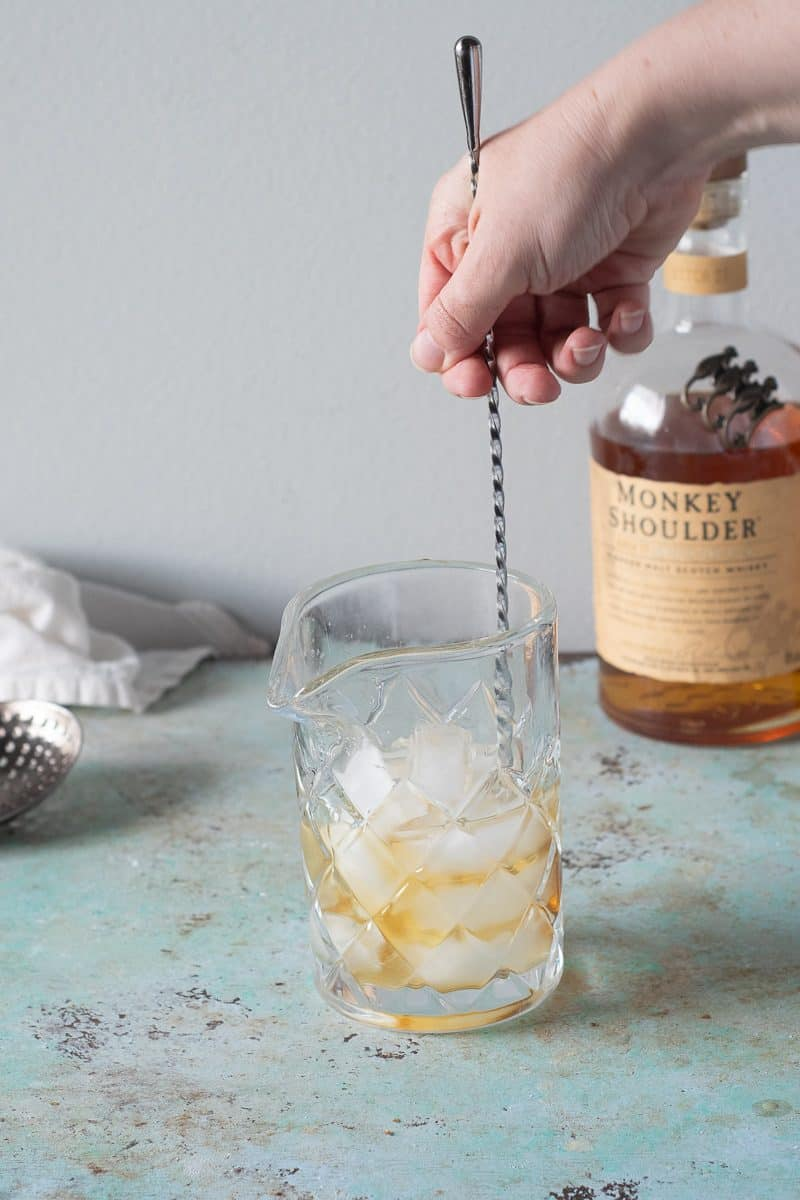 Stirring the Scotch and Drambuie with ice in a mixing glass