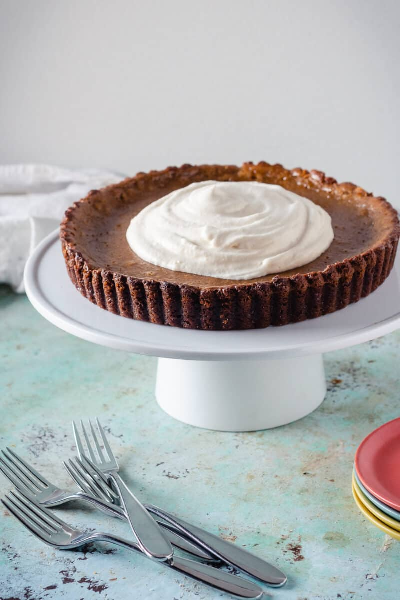Caramel Pumpkin Tart with Gingersnap Crust on a cakestand