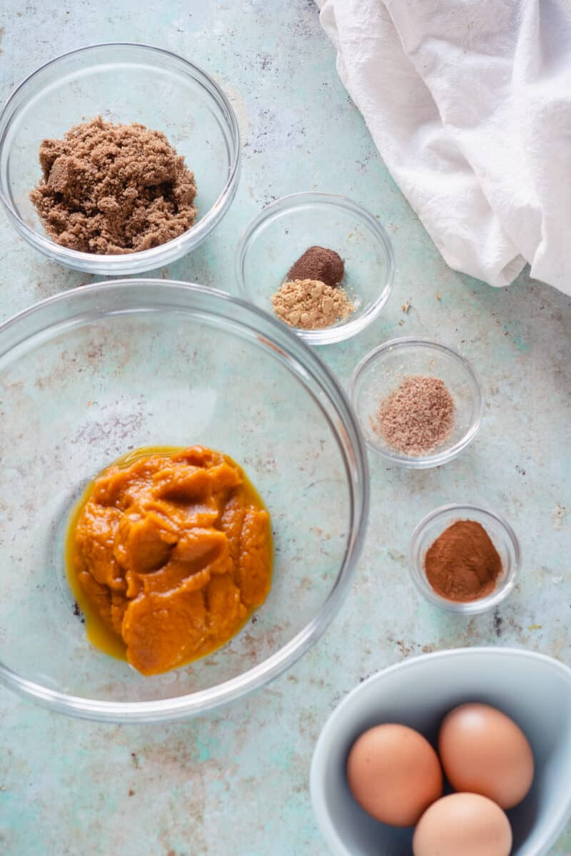 Bowls of brown sugar, spices, eggs, and pumpkin puree