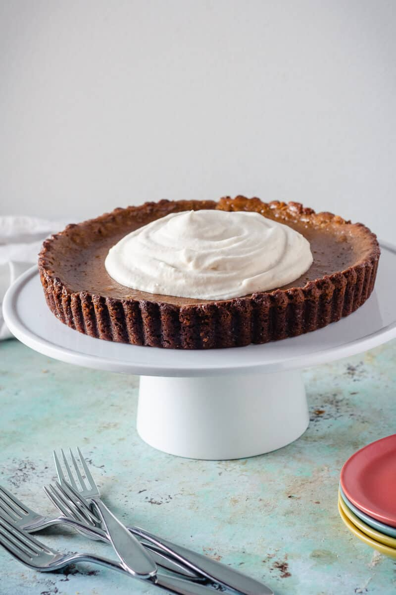 Caramel pumpkin tart on a white cake stand