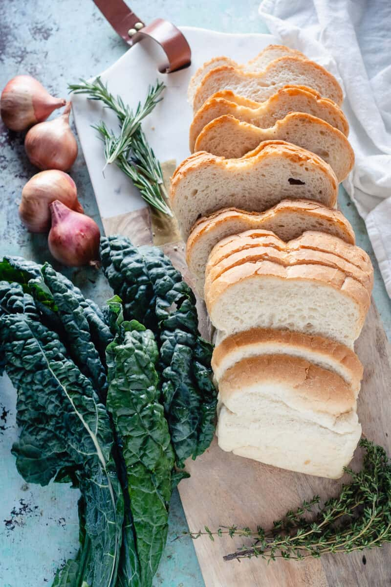 Kale, shallots, rosemary, and bread on a cutting board