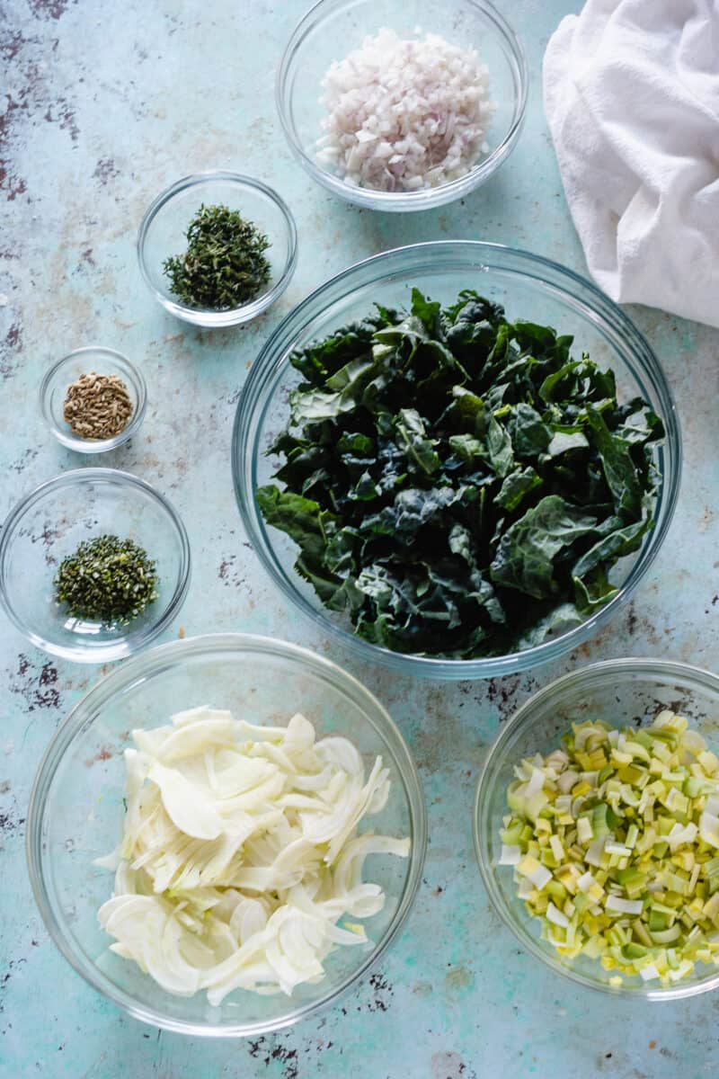 Bowls of sliced kale, fennel, leeks, shallots, and herbs